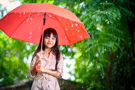 lluvia paraguas: Peque�a muchacha asi�tica con el paraguas en la lluvia Foto de archivo