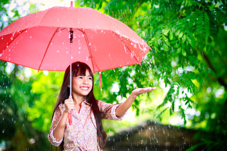walking in the rain: Little asian girl with umbrella in the rain Stock Photo
