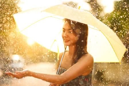 Asian woman walking with umbrella under rain photo