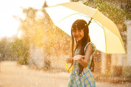 Pretty young asian girl in the rain with umbrella Фото со стока
