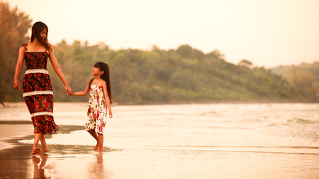Mother with her daughter walking on the beach photo