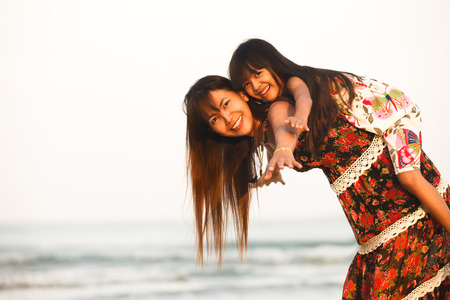 Happy mother holding her daughter on the beach photo
