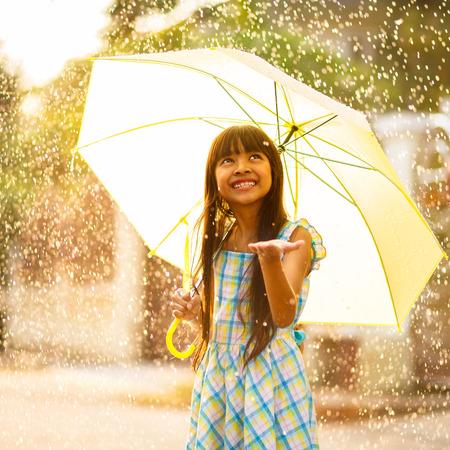 Pretty niña de origen asiático en la lluvia con paraguas Foto de archivo - 27858741