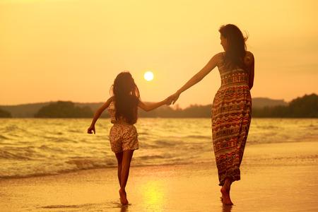 caminar: Madre e hija caminando en la playa con la puesta del sol