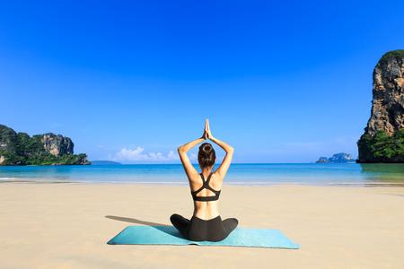 Donna Yoga sulla costa del mare Archivio Fotografico - 27874078