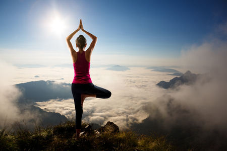 Young woman exercises yoga in the mountains photo