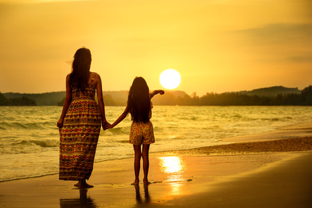 bright: Rear view of a mother and daughter standing on the beach Stock Photo