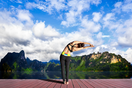 Young woman is practicing yoga at mountain lake Stock Photo - 28130279
