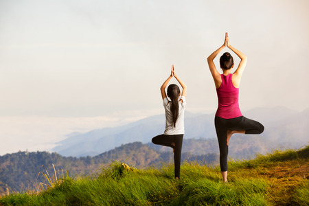 Mother and daughter doing yoga at top of mountain Stock Photo