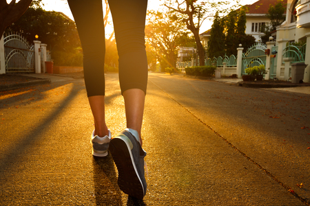 Woman with an athletic pair of legs going for a jog during sunset photo
