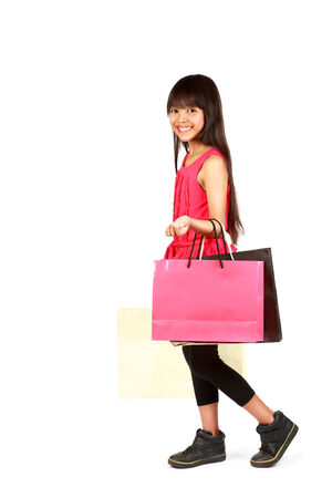 Little asian girl with shopping bags, Isolated over white photo