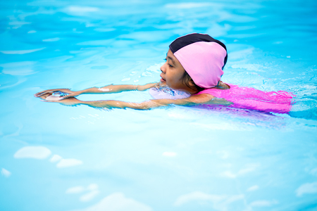 Little asian girl on swimming pool blue water background photo