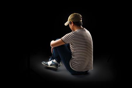 10 代の少年一人で座っています。