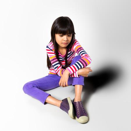 petite fille triste: Triste petite fille assise sur le sol