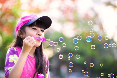 Bonito Niña asiática que sopla burbujas de jabón, retrato al aire libre Foto de archivo