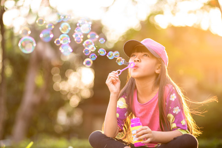 Little asian girl blowing soap bubbles outdoor at sunset photo