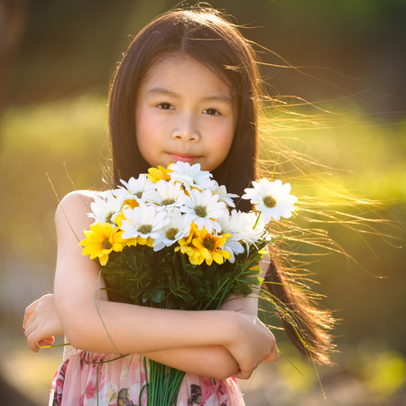 Happy little asian girl holding a bunch of flowers photo