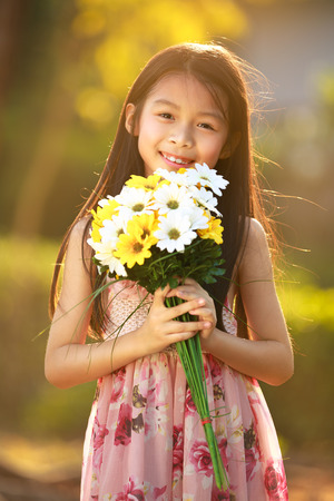 Smiling asian girl hold flowers, Fashion child portrait photo