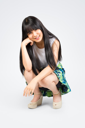 Smiling teenage asian girl sitting, Isolated over white photo