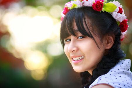 Closeup beautiful smiling teenage girl against green of summer park photo