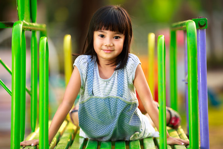 Little asian girl sitting on slide at playground photo