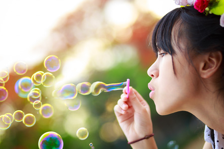 Close up teenager girl blowing soap bubbles in the park photo