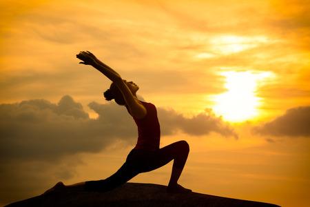 Junge asiatische Frau Yoga Krieger stellen bei Sonnenuntergang Standard-Bild - 28652426