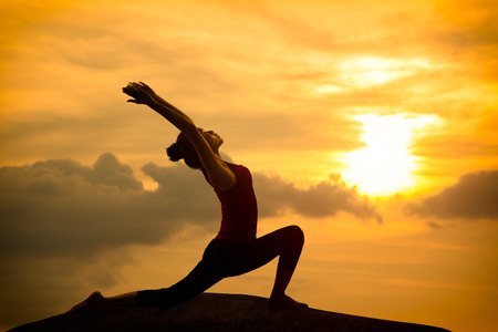 Young asian woman practicing yoga warrior pose at sunset photo
