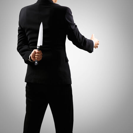 holding a knife: a man in suit holding knife behind back, Isolated on grey background Stock Photo