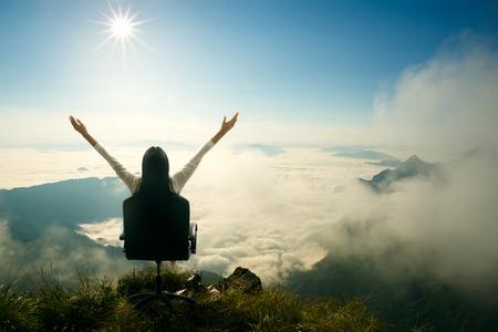 De jonge vrouw zit op een stoel en opent haar armen op de top van de berg, Succes in business concept Stockfoto
