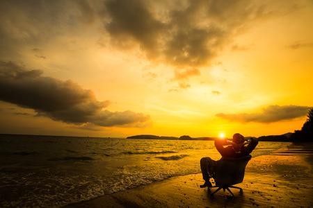 úspěšný: Relaxační podnikatel sedí na pláži, úspěch v podnikání koncept Reklamní fotografie