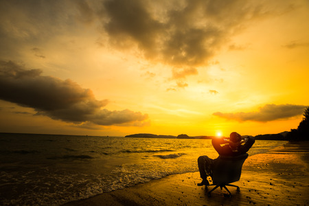 Relaxing businessman sitting on beach, Success in business concept Stock Photo