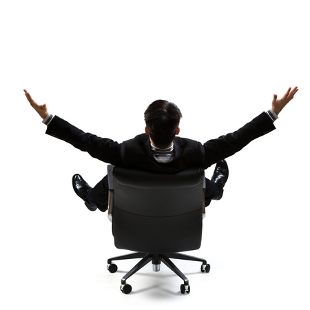 legs wide open: Business man in rear view sitting on a chair and open arms, Isolated over white