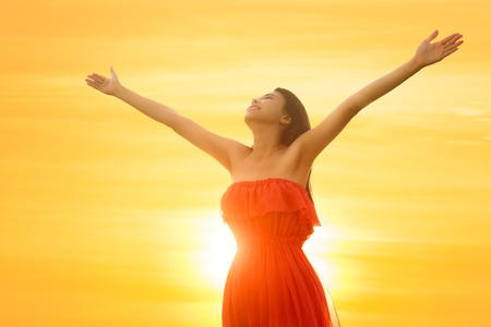Young asian woman standing open her arms under the sunrise photo