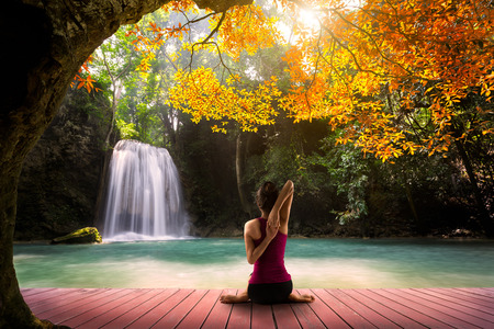 Young woman in yoga pose sitting near watefall, Rear view photo