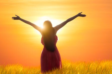 Jonge Aziatische vrouw haar armen te openen onder de zonsopgang Stockfoto