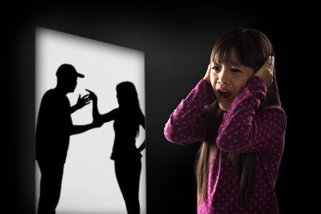 divorcio: Crying illtle muchacha asi�tica con sus padres que luchan en el fondo Foto de archivo
