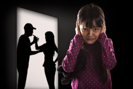 personas discutiendo: Crying illtle muchacha asiática con sus padres que luchan en el fondo Foto de archivo