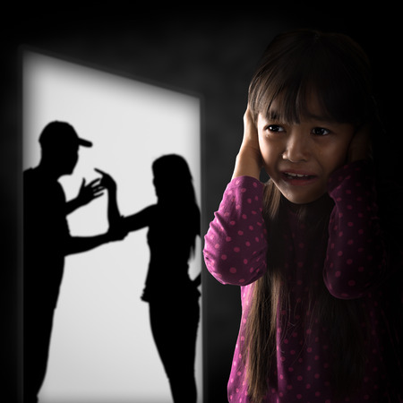 Crying illtle asian girl with her fighting parents photo