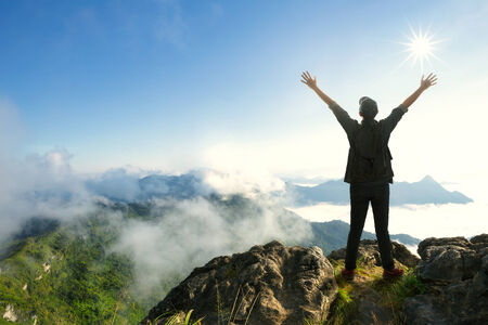 Teenager boy with backpack standing on top of a mountain with raised hands photo