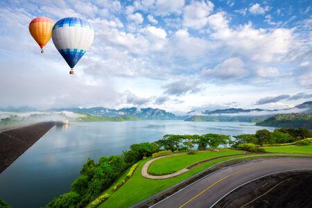 Hot air balloon ffloating over dam photo