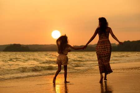 Mother and daughter running on the beach with sunset photo
