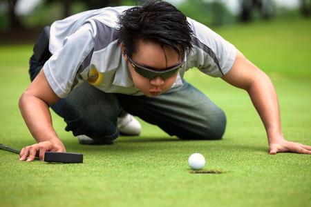 desperate: Golfista Desperate sopla en la pelota de golf para poner en el agujero, divertido concepto tramposo de golf Foto de archivo