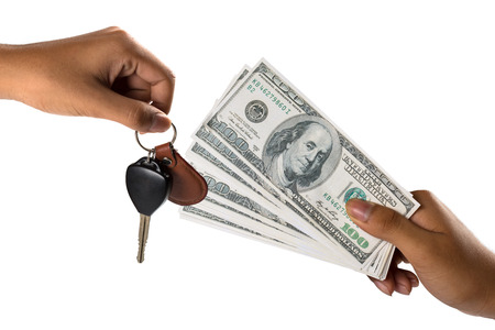 Hand with money and car keys, Isolated over white photo