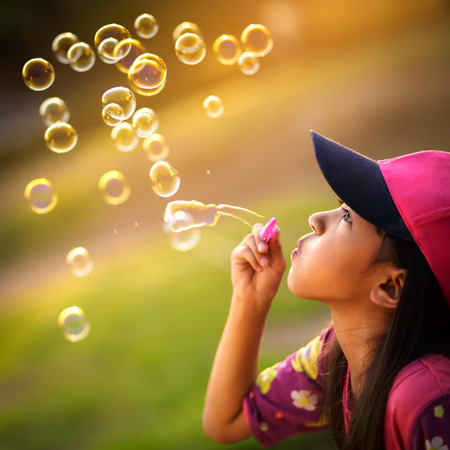Asian little girl is blowing a soap bubbles photo