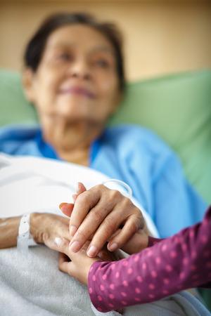 niños enfermos: Cuidar las manos que sostienen tipo señora mayor Foto de archivo