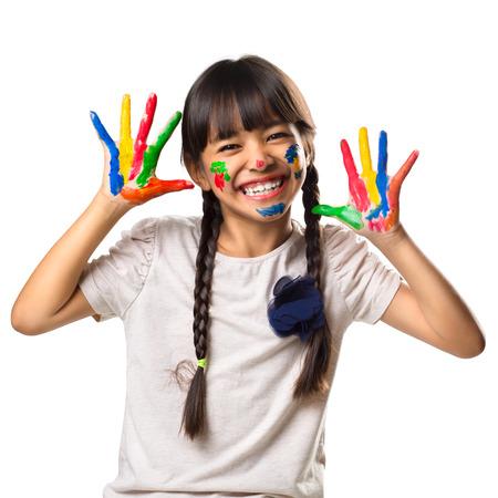 caritas pintadas: Pequeña muchacha asiática con las manos en la pintura, aislados en blanco Foto de archivo