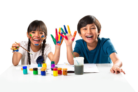 Two smiling little kids at the table draw with water color, Isolated over white Foto de archivo