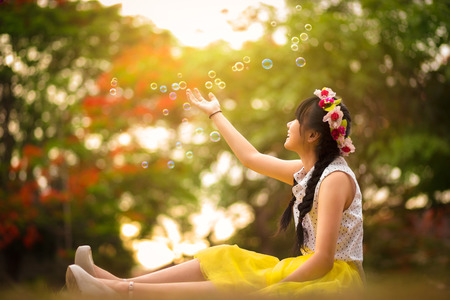 Asian teenager girl in the park under soap bubble rain photo