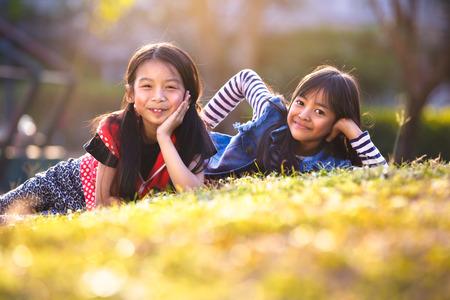 niños jugando en el parque: Dos niñas asiáticas que ponen en la hierba verde bajo la luz del sol
